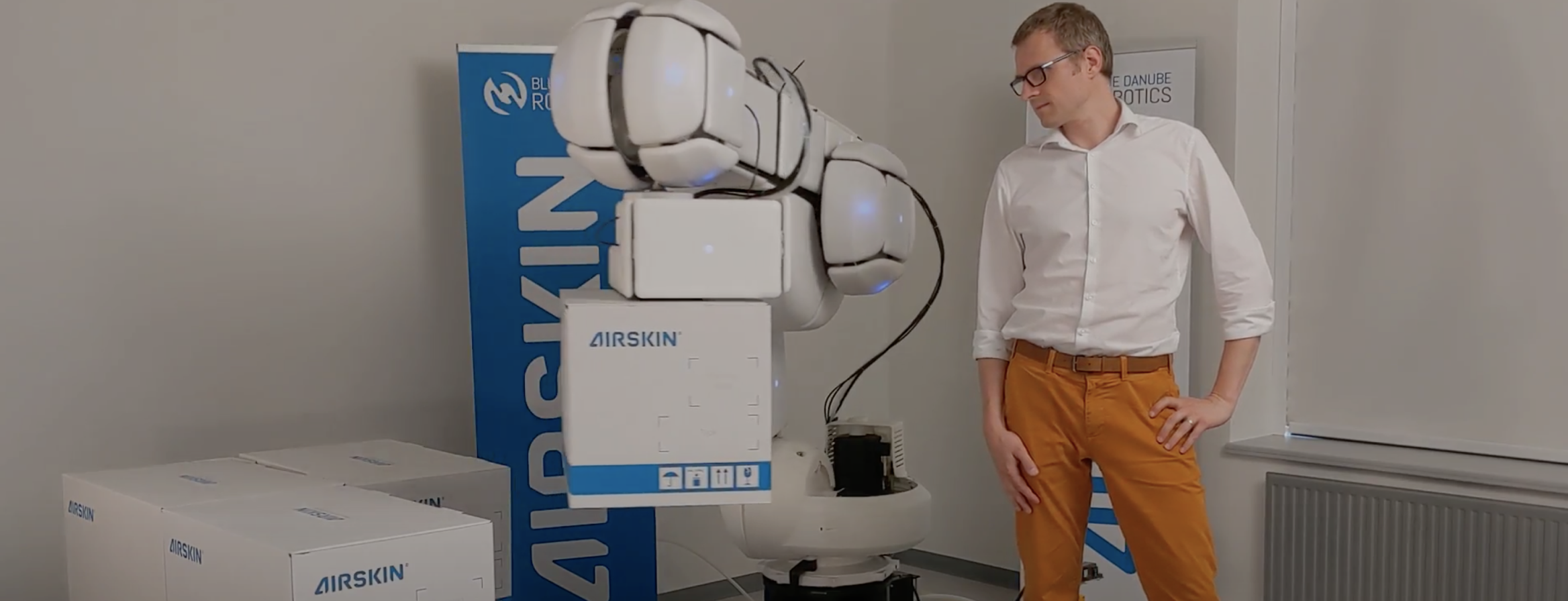 Man standing next to a robot equipped with AIRSKIN